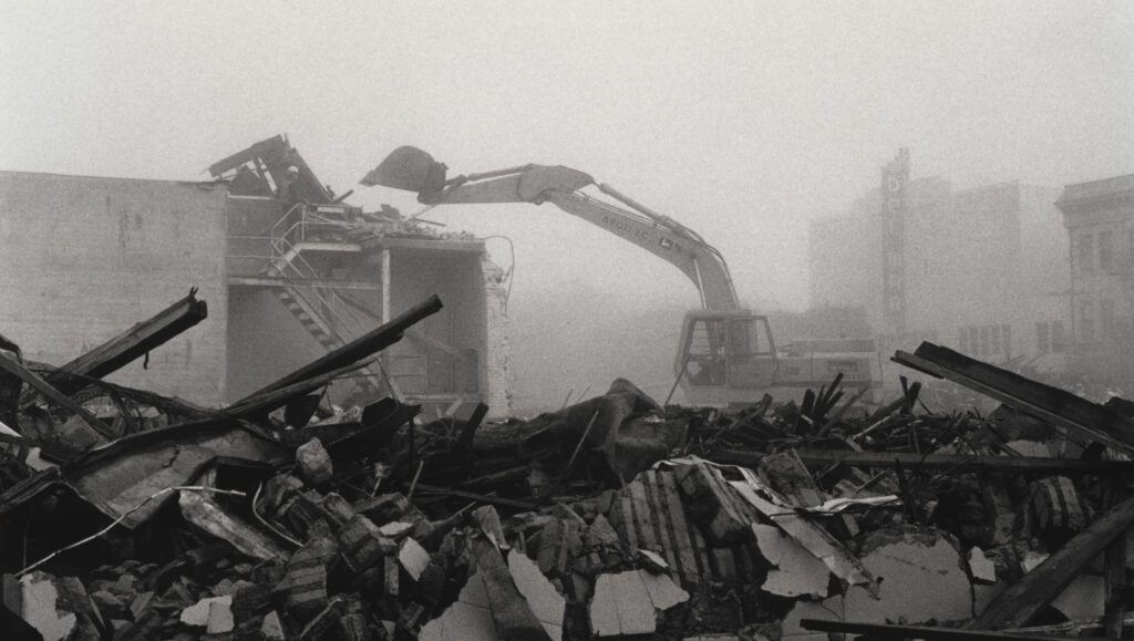 Rubble of a collapsed building, with excavator in the background, in downtown Santa Cruz