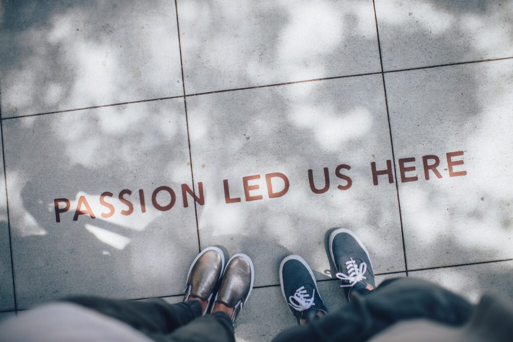 """Picture of the text """"Passion led us here"""" on a sidewalk, with feet"""